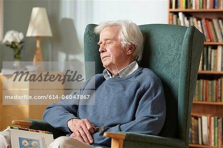 Senior man sleeping in armchair