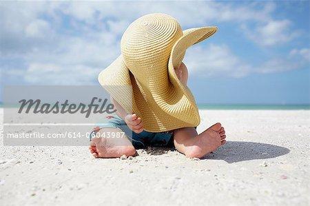 Petit garçon jouant avec chapeau de soleil de la mère sur la plage
