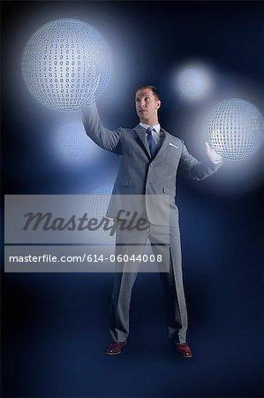 Homme d'affaires interagissant avec des globes binaires holographiques