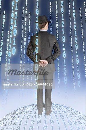 Businessman standing on binary globe with binary strings