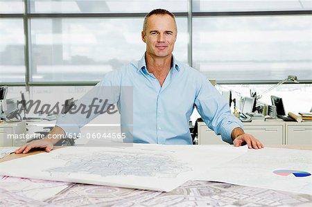 Porträt eines Architekten an Blaupausen im Büro arbeiten