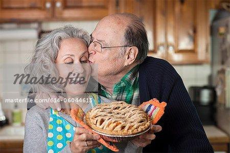 Senior homme embrasser femme tenant fraîchement cuit au four tarte