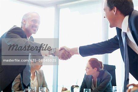 Hommes d'affaires, serrant la main dans la salle de conférence