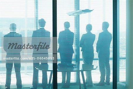 Silhouette der Geschäftsleute in Folge Bürofenster mit Blick