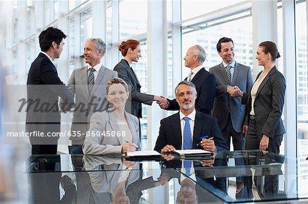 Gens d'affaires serrant la main dans la salle de conférence