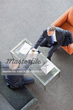 Les hommes d'affaires lui serrer la main à travers la table à café dans le Hall