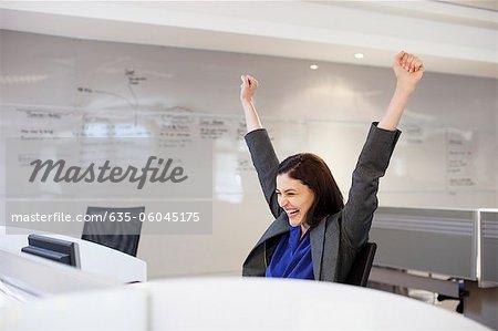 Femme d'affaires enthousiaste avec les bras levés au bureau