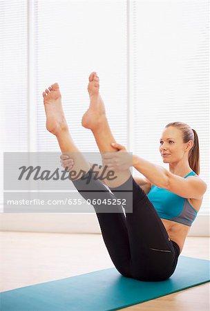 Femme qui s'étend sur le tapis d'yoga