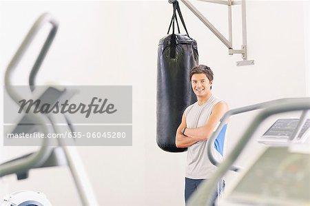 Portrait d'un homme souriant au sac de boxe au gymnase