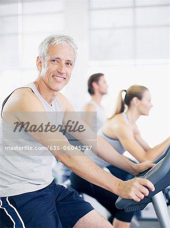 Portrait d'homme sur un vélo d'exercice dans le gymnase de sourire