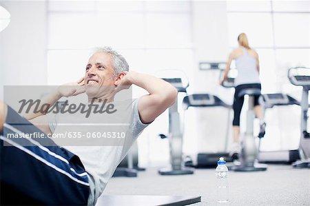 Homme souriant faire des redressements assis sur le plancher dans le gymnase
