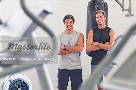 Portrait de sourire des hommes avec les bras croisés devant le sac de boxe