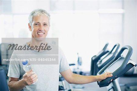 Portrait d'un homme souriant, tenant la bouteille d'eau sur tapis roulant en gymnase