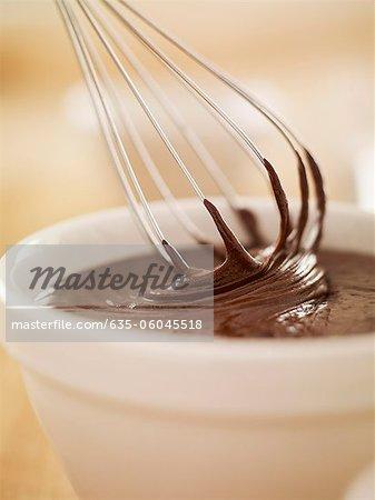 Nahaufnahme von Schneebesen Eintauchen in Schüssel mit geschmolzener Schokolade