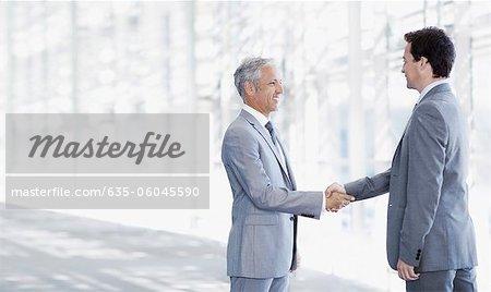 Smiling businessmen shaking hands in modern corridor
