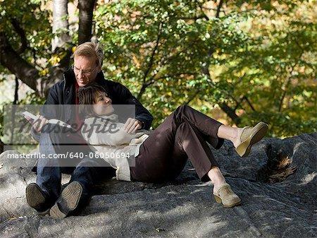 États-Unis, New York City, Manhattan, Central Park, couple d'âge mûr lecture livre à Central Park
