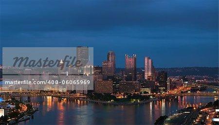 Panoramic image of Pittsburgh skyline at night.