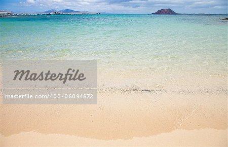 Fuerteventura beach - beautiful white sand beach in the town bounds of Corralejo, small island Isla de Lobos in the background