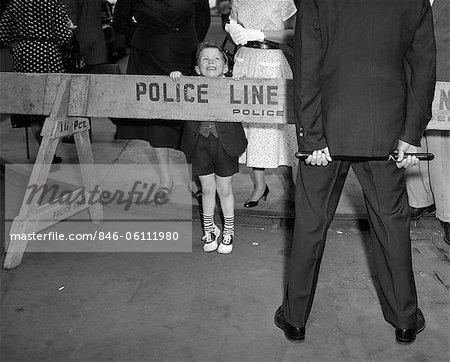 ANNÉES 1950 GARÇON REGARDANT EN ARRIÈRE SUR LA BARRICADE DE LA POLICE À L'AGENT DE POLICE QUI EST À LA FOULE DE CAMÉRA DES GENS EN ARRIÈRE-PLAN EN PLEIN AIR