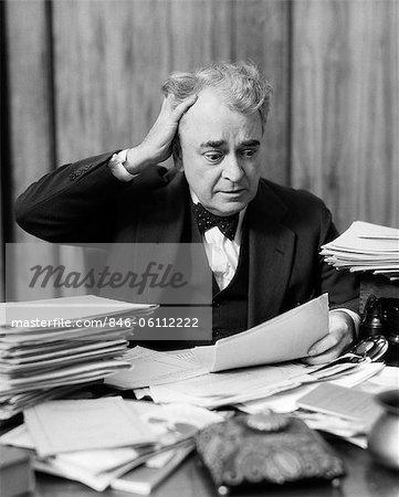 ANNÉES 1930 ÂGÉES HOMME ASSIS AU COMPTOIR ENTRE LES PILES DE PAPIERS AVEC DES CHEVEUX EN MAIN & EXPRESSION ÉNERVÉE