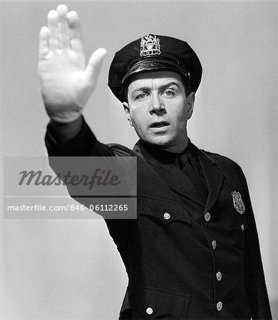ANNÉES 1950 HOMME POLICIER EN UNIFORME, TENANT LA MAIN VERS LE HAUT DANS L'AIR VERS L'APPAREIL STOP HALT AVERTISSEMENT REGARDANT LA CAMÉRA