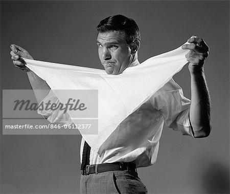 ANNÉES 1960 MAN HOLDING COUCHE EN TISSU PLIÉ EN TRIANGLE SOUS MENTON AVEC DES ÉPINGLES DE SÛRETÉ EN BOUCHE EN REGARDANT CAMÉRA AVEC COLÈRE