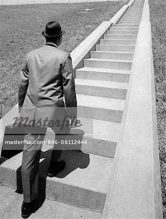 HOMME D'AFFAIRES DES ANNÉES 1960 EN COSTUME & FEDORA HOLDING PORTE-DOCUMENTS DÉMARRE LONGUE VOLÉE D'ESCALIER DE CIMENT AVANT DE LUI