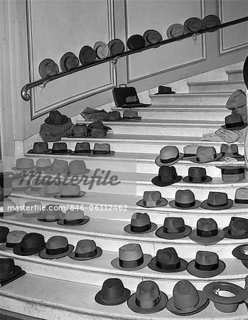 1950s MEN'S HATS COATS LINED UP ON LARGE STAIRWAY INDOOR