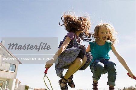 Jeunes filles sautant corde ensemble en plein air