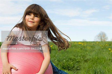 Mädchen spielen auf bouncy Ball im Feld