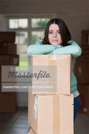 Teenage girl leaning on cardboard box