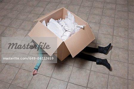 Adolescente se trouvant sous la boîte en carton