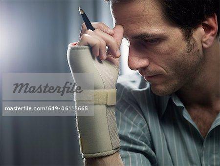 Homme d'affaires dans l'attelle de poignet avec un crayon