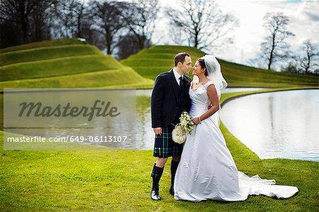 Couple de jeunes mariés s'embrasser dans le champ