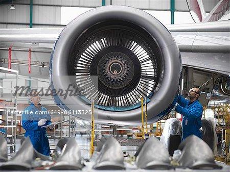Travailleurs examinant de moteur d'avion