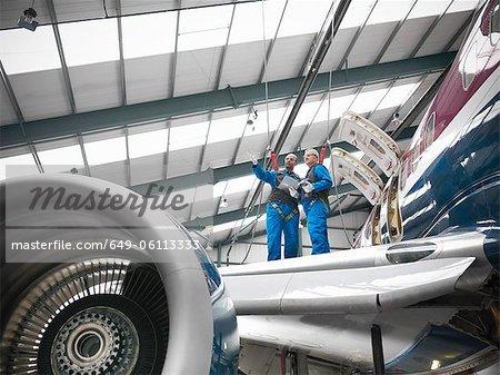 Workers examining airplane in hangar