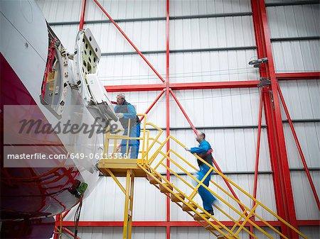 Travailleurs examinant l'avion dans le hangar