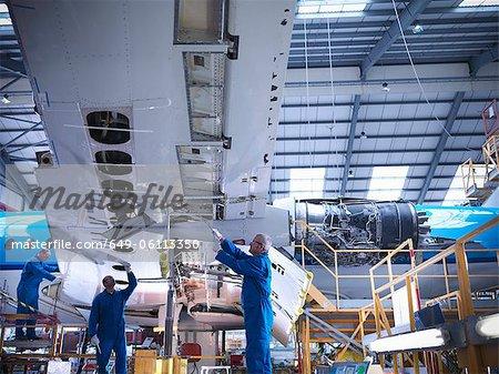 Workers examining airplane machinery