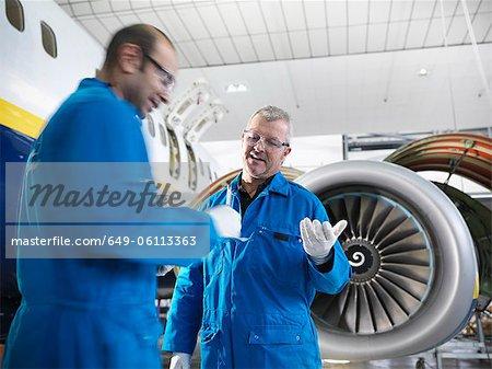 Workers talking in airplane hangar