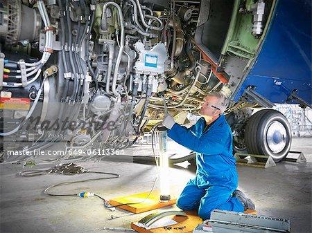 Worker examining airplane machinery