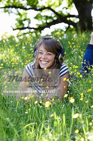 Frau hören Kopfhörer im Gras