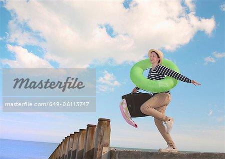 Teenage girl with suitcase on dock