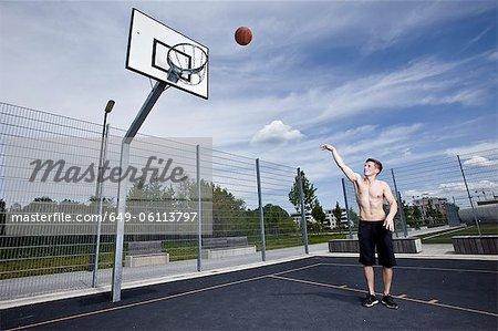 Mann am städtischen Gericht Basketball spielen
