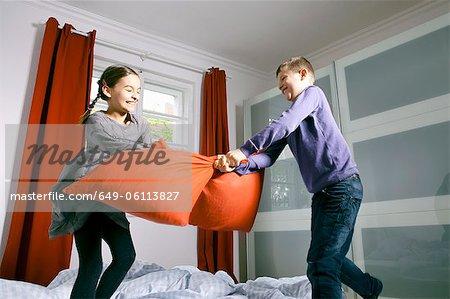Enfants ayant pillow fight sur lit