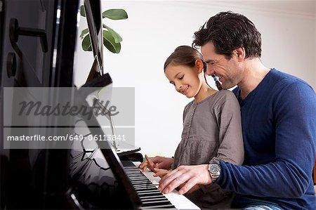 Père et fille jouer du piano