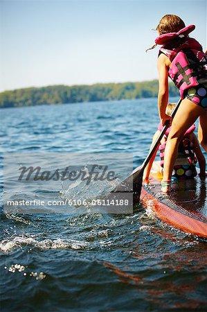 Famille sur le lac sur le stand up paddle monte à été