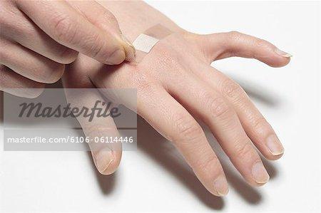 main avec band aid, en gros plan des mains