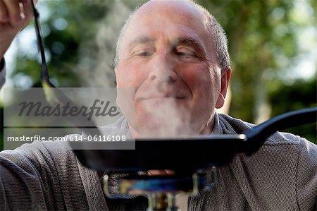 Senior man cooking on camping stove