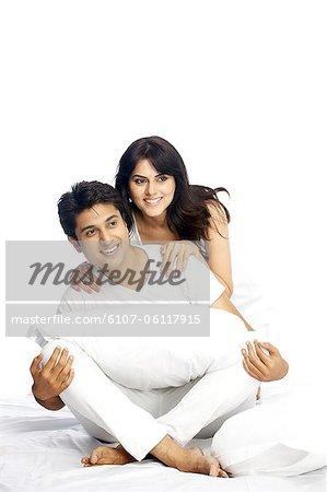 Portrait d'un couple heureux assis sur le lit