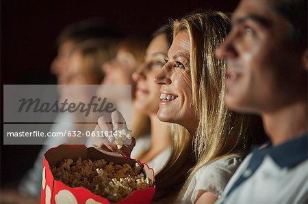 Femme mangeant maïs soufflé tout en regardant le film dans le théâtre